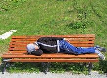 A bu des repos d'homme sur un banc en parc images stock