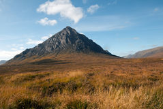 Buachaille etive mor. E showing it's atumn colours infront and ble clouded skies above Royalty Free Stock Photos