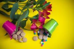 Buacket verde y rosado por completo de píldoras con la flor imagen de archivo libre de regalías