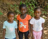 Bubaque, Guinea-Bissau - December 09, 2013: Portret van tthree niet geïdentificeerde jonge Afrikaanse meisjes op vuilweg stock afbeelding