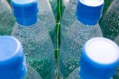 Bubbla i flaskor av vatten Arkivfoto