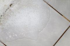 Bubblatvåltvättmedel med skurning av badrumgolvsmutsen våt, vit bubbla för skum från schampotvagning på Tiled bästa sikt för golv royaltyfri fotografi