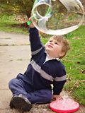 Bubble. Young boy watching the large bubble he made on wand Royalty Free Stock Image