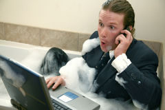 Bubble Bath. Thirty something business man in bubble bath with cellphone and laptop computer royalty free stock photography