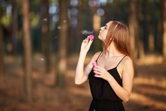 Portrait of pretty woman with bubbles, traveler relaxing in forest. Stock Photos