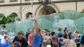 Bubble entertainment, happy people playing with soap bubbles in city on town square stock footage