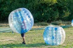 Bubble Football. Teenagers play in Bubble bump, new and fun team game outdoor. Children are inside of blown plastic transparent bubble shock each other with fun royalty free stock photos