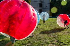 Bubble Football. Teenagers play in Bubble bump, new and fun team game outdoor. Children are inside of blown plastic transparent bubble shock each other with fun stock images