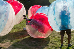 Bubble Football. Teenagers play in Bubble bump, new and fun team game outdoor. Children are inside of blown plastic transparent bubble shock each other with fun stock photo