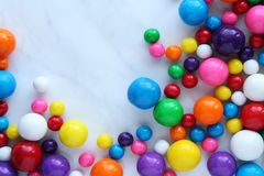 Bubble Gumballs. Bright and colorful gumballs in different sizes frames white marble copy space stock photos