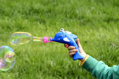 Bubble gun. Children is playing Plastic bubble gun Royalty Free Stock Photography