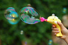 Bubble Gun. Plastic toy gun makeing lots of  soap bubbles Royalty Free Stock Image