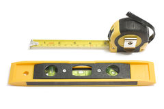 Bubble level and measure tape on white. Background Stock Images