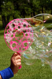 Bubble Maker. A child's hand holds a bubble maker in the wind and large soap bubbles blow out Royalty Free Stock Image