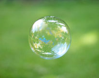 Bubble Reflection. A detailed landscape is reflected in a bubble, isolated against a blurred green grass background Royalty Free Stock Photos