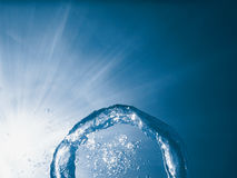 Bubble ring underwater ascends towards the sun. Stock Photo