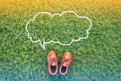 Bubble speech and toy shoes. On grass field texture background with copy-space Stock Photo