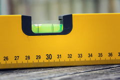 Bubble spirit water level construction tool on wooden board closeup Royalty Free Stock Photos