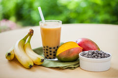 Bubble Tea. Mango smoothie bubble tea with fruit and tapioca pearls in the garden Royalty Free Stock Photography