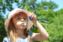 Bubble wand. Adorable little girl playing with a bubble wand. Horizontal royalty free stock images