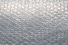 Bubble wrap on blue background. Bubble wrap is a pliable transparent plastic material used for packing fragile items. Regularly spaced, protruding air-filled stock photography
