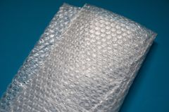 Bubble wrap on blue background. Bubble wrap is a pliable transparent plastic material used for packing fragile items. Regularly spaced, protruding air-filled stock image