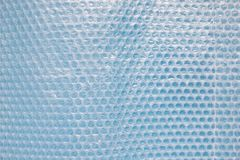Bubble wrap on blue background. Bubble wrap is a pliable transparent plastic material used for packing fragile items. Regularly spaced, protruding air-filled royalty free stock photos