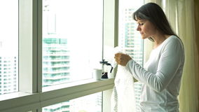 Bubble wrap therapy. Mature woman by the window is releasing stress by popping bubble wrap stock footage