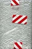 Bubble wrap with white and red tape Stock Images