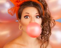 Bubblegum. Happy woman at party blowing bubblegum bubble with air baloons on background Stock Photos