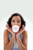 Bubblegum girl. Beautiful Latina girl with huge eyes open blowing a bubblegum bubble, isolated Royalty Free Stock Image