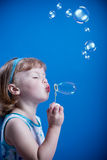Bubbles. A little girl blowing soap bubbles Royalty Free Stock Image