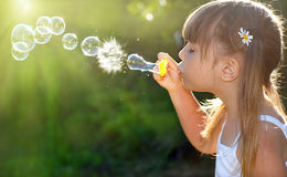 Bubbles. Little girl blowing soap bubbles, she playing Royalty Free Stock Photo