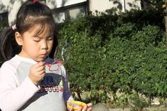 Bubbles. Young asian girl blowing bubbles stock photos