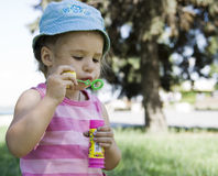Bubbles. Little girl blow soap bubbles Royalty Free Stock Image