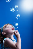 Bubbles. A little girl blowing soap bubbles Royalty Free Stock Photography