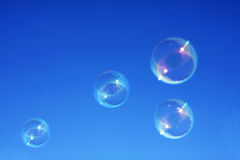 Bubbles against a blue sky. Bubbles against a graduated blue sky background stock photo