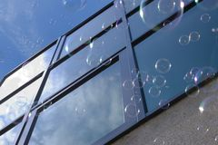 Bubbles against window. Soap bubbles escaping to sunny sky against blue glass windows royalty free stock photo