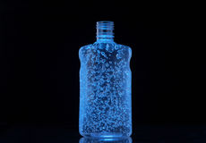 Bubbles in a bottle. A blue bottle of thick, transparent liquid is filled with suspended bubbles.  The background is black with space for advertising slogans Stock Photography