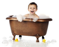 Bubbles, Bubbles, Everywhere. An adorable preschool boy laughing in a copper, claw-foot tub full of bubbles.  Isolated on white Stock Image
