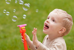 Bubbles and child. Child blowing bubbles and trying to pop them.  Excitement and wonder in his wide eyes Royalty Free Stock Photos
