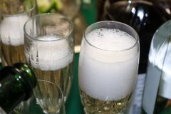 Bubbles coming off poured champagne in a foamy glass with surrounding bottle shapes and more champagne being poured Royalty Free Stock Images