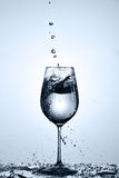 Bubbles of drinking water falling in the wineglass standing on the glass with droplets against light background. Stock Photography