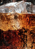 Bubbles in the glass of cola with ice. Royalty Free Stock Images