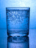 Bubbles in a glass of water. Glass of water with bubbles, in blue Royalty Free Stock Photos
