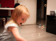 The bubbles. Little girl 2 years old have fun in her home with soap bubbles Royalty Free Stock Photos