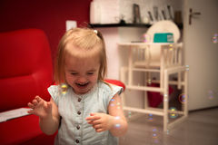 The bubbles. Little girl 2 years old have fun in her home with soap bubbles Stock Photo