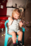 The bubbles. Little girl 2 years old have fun in her home with soap bubbles Stock Image
