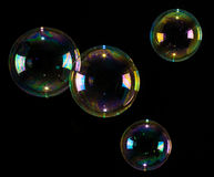 Bubbles floating over black background. 4 bubbles with multiple colors floating in mid-air over a white background Stock Images
