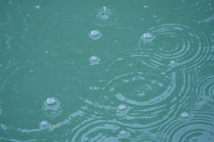 Bubbles in a Pond. Raindrops falling in blue water Stock Photography